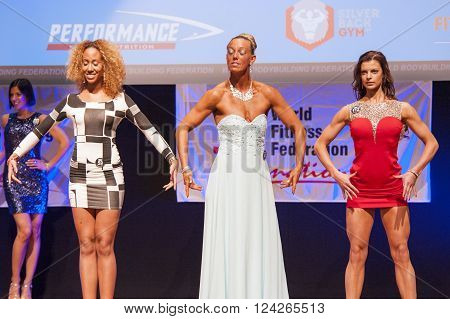 MAASTRICHT THE NETHERLANDS - OCTOBER 25 2015: Female fitness models in evening dress show their best physique in championship on stage at the World Grandprix Bodybuilding and Fitness of the WBBF-WFF on October 25 2015 at the MECC Theatre in Maastricht