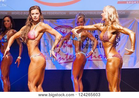 MAASTRICHT THE NETHERLANDS - OCTOBER 25 2015: Female fitness bikini models show their best side pose at championship on stageat the World Grandprix Bodybuilding and Fitness of the WBBF-WFF on October 25 2015 at the MECC Theatre in Maastricht