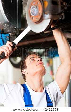 Auto mechanic in his workshop looking under a car on a hoist