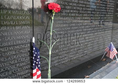 WASHINGTON, DC - MARCH 25, 2016: Lone red carnation and American flag at Vietnam Veterans Memorial