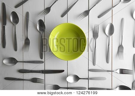 Plate and silver flatware on white table, top view