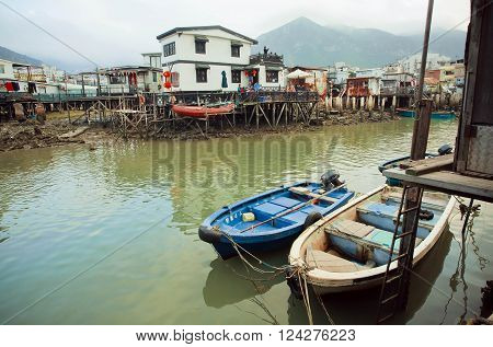 HONG KONG, CHINA - FEB 11: Riverboats in dirty river of old fishermen village Tai O with rustic houses on February 11, 2016. Hong Kong dollar is the eighth most traded currency in the world