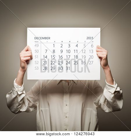 Woman is holding December calendar of the year two thousand fifteen