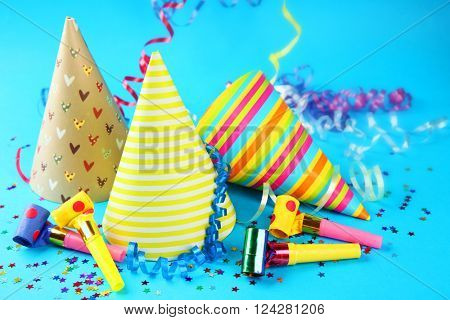 Three Birthday hats with serpentine streamer and noise makers on blue background