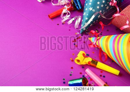 Birthday hats with serpentine streamer and noise makers on purple background