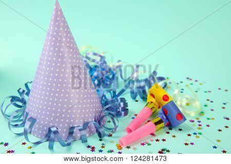 Dotted Birthday hat with serpentine streamer and noise makers on light blue background