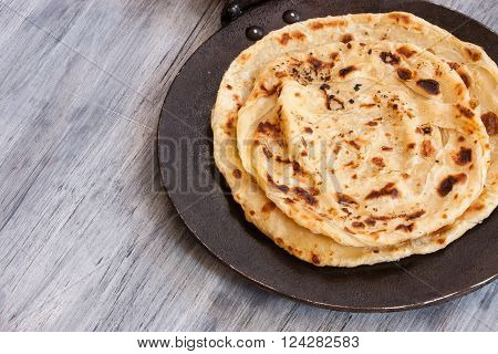 Indian layered Paratha roti on black pan