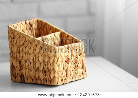 Wicker box on wooden table against brick wall background