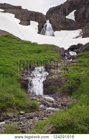 A small waterfall with snow in Iceland