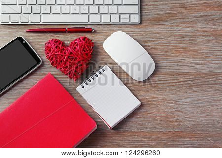 Computer peripherals with red wicker heart, notebooks and mobile phone on wooden table