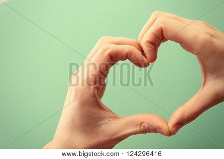 Male and female hands making heart with fingers on turquoise background