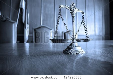 Decorative Scales of Justice on the table. Focus on the scales BLUE TONE