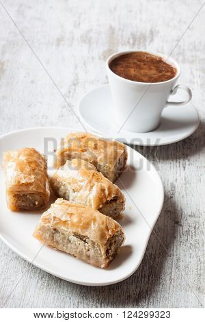 Baklava with walnut and Turkish coffee on a white wooden background