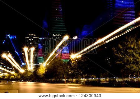 Abstract shot of Flame Towers lit up with colours of Azerbaijani flag. Modern buildings seen from Baku Bulvar, long exposure whilst zooming