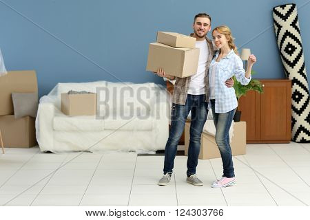 Happy young couple with boxes and keys moving in their new apartment
