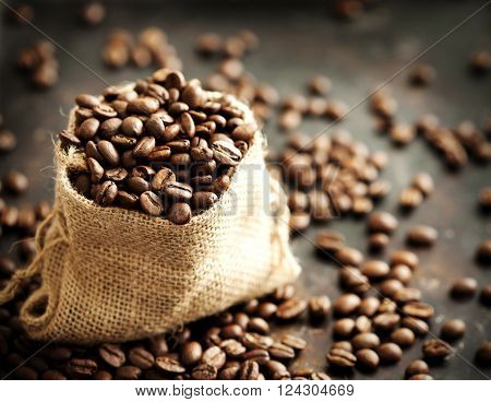 Coffee beans  in a burlap bag on dark background