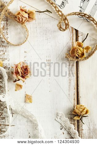 Dry roses and laces on wooden background. Vintage background