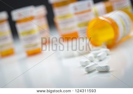 Variety of Medicine Bottles Behind Pills Spilling From Fallen Bottle.