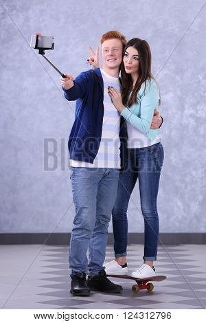 Teenager couple with skateboard using stick for photo by their self on grey background