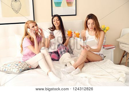 Two friends using mobile phones and one girl reading book on a bed in living room