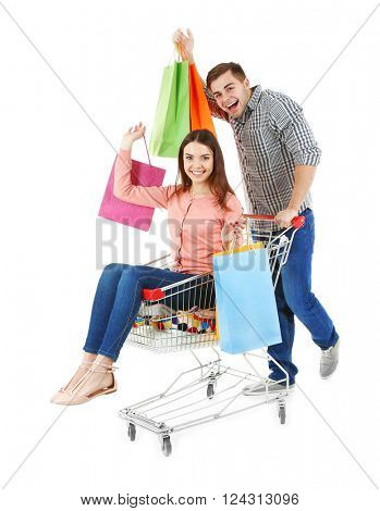 Man carrying woman in metal trolley with colorful shopping bags isolated on white