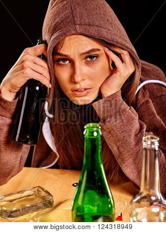 Drunk girl holding green glass bottle of alcohol. Soccial issue alcoholism.