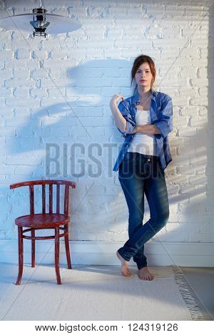 Casual young woman leaning against white brick wall, standing by chair.