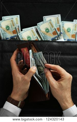 Businessman holding wallet and brief case with money