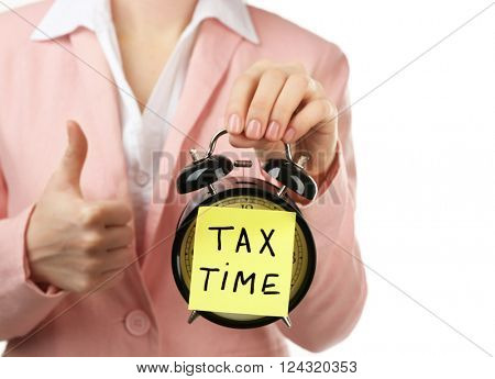 Woman in pink suit holding alarm with tax time inscription, isolated on white
