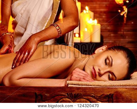 Young woman having oil Ayurveda spa treatment. Lighting candles.