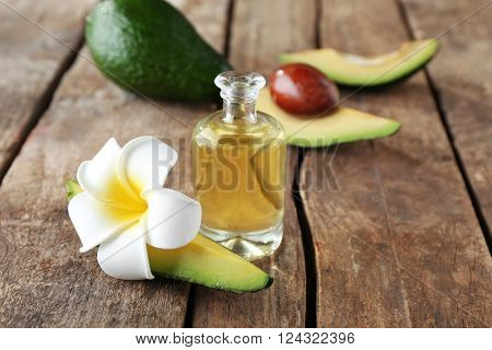 Avocado, plumeria and oil on wooden table