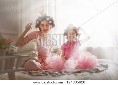 Funny family! Mother and her child daughter girl with a paper accessories. Mother and daughter preparing for a party and having fun. Beautiful young woman and funny girl with a paper crowns on sticks.
