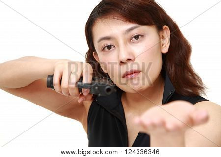 studio shot of female robber with a handgun