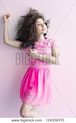 A young girl of Caucasian appearance dancing and dreams of a bright room on a summer day. Wavy curly hair and a pink dress. Rest and be happy.