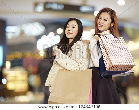 two smiling young asian women carrying shopping bags.