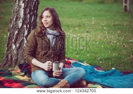 Young brunette woman resting under a tree during trip. Caucasian backpacker woman holding a mug outdoor.