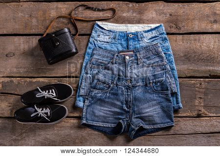 Lady's different denim shorts. Aged shelf with denim garments.Different classic shorts and footwear. Shorts sale at retro boutique.