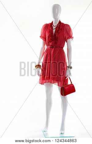 Red v-neck dress on mannequin. Female mannequin in red dress. Bright dress and colorful accessories. Stylish garment in red color.