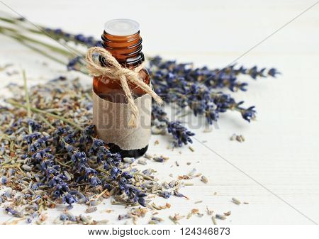 Bottle of aroma lavender oil, empty parchment lable, dried lavender flowers.