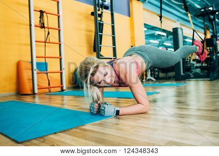 Fitness girl training trx workout in gym. Fitness coach show trx workout in gym. Athletic girl working on trx workout in gym
