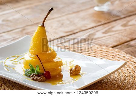 Pear in an orange juice on a white square plate. Vegetarian's dessert