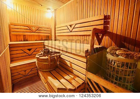 Finnish wooden modern sauna interior. Empty sauna with nobody in. Wooden sauna room. Interior of sauna steam wooden room. Spa and relax, healthcare complex.