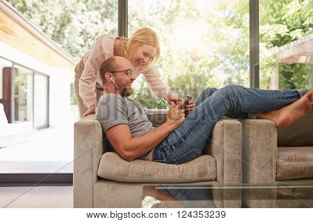 Indoor shot of mature couple at home using digital tablet and smiling. Man is sitting on sofa with woman standing by. Both looking at tablet computer and laughing.