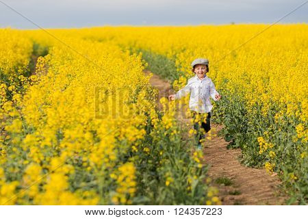 Adorable little boy running in yellow oilseed rape field feeling happy and free
