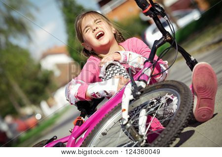 Young girl fell from the bike in a park