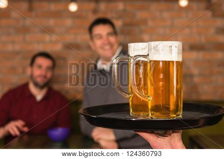 Waiter bringing beer for friends in the pub