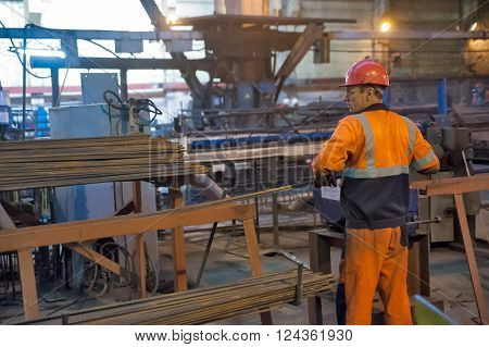 Tyumen, Russia - August 13, 2013: Block making department at construction material factory ZHBI-5. Worker in reinforcing shop
