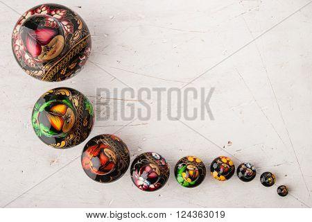 Matreshka set on the white wooden table top view