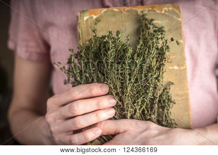 Woman holding old recipe book and herbs horizontal
