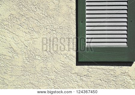 Simple and clean photo of a green shutter on exterior stucco wall with uncluttered background